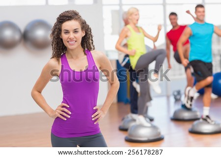 Portrait of happy fit woman standing hands on hips with people exercising in background at gym - stock photo