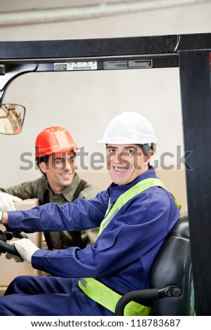 Portrait of happy forklift driver with colleague at warehouse - stock photo