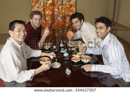 Portrait of happy four men eating sushi with chopsticks in the restaurant - stock photo