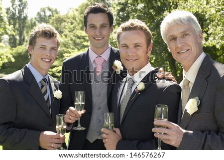 Portrait of happy four men holding champagne flutes at wedding day - stock photo