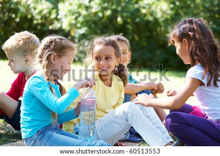 Portrait of happy friends chatting with each other in park - stock photo