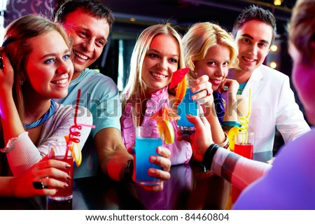 Portrait of happy friends holding glasses with cocktails in bar - stock photo