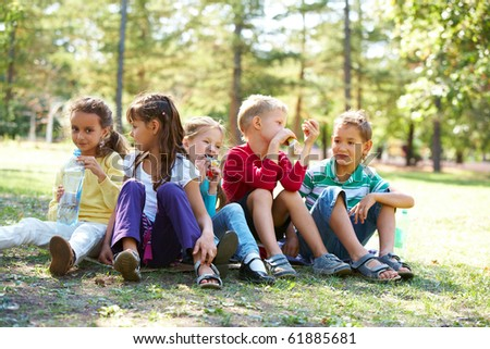 Portrait of happy friends sitting on the ground in park and having meal time - stock photo
