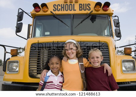 Portrait of happy friends standing in front of school bus - stock photo
