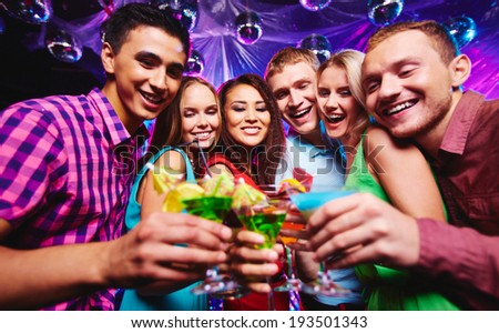 Portrait of happy friends with cocktails having fun at party - stock photo