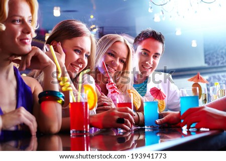 Portrait of happy friends with cocktails having rest in bar - stock photo
