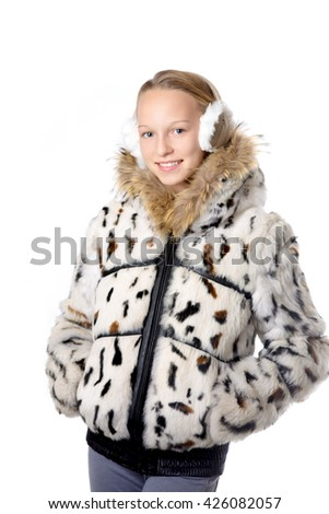 Portrait of happy funny beautiful casual teenage girl wearing winter coat and earmuffs, holding hands in pockets, looking at camera with cheerful expression, studio image, white background - stock photo