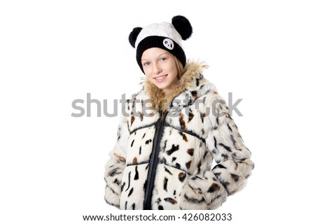Portrait of happy funny beautiful casual teenage girl wearing winter coat and knitted panda hat, holding hands in pockets, looking at camera with cheerful expression, studio image, white background - stock photo