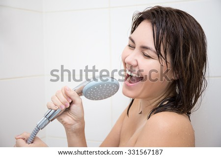 portrait of happy funny woman singing in shower - stock photo
