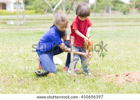 Portrait of Happy Girl and Boy Planting Outdoors - stock photo