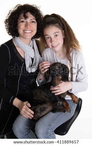 Portrait of happy girl and her mother cuddling dog  - stock photo