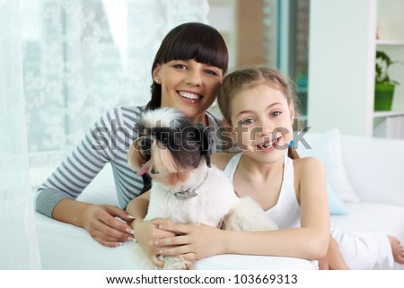 Portrait of happy girl and her mother holding pet and looking at camera with smiles - stock photo