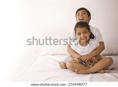 Portrait of happy girl being embraced by brother in bed - stock photo