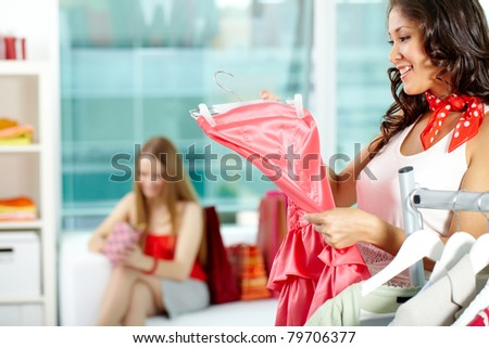Portrait of happy girl choosing new dress in clothing department - stock photo
