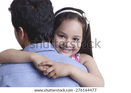 Portrait of happy girl embracing father against white background - stock photo