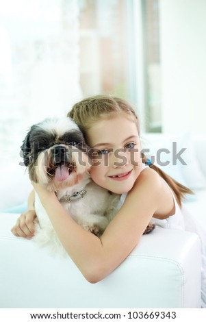 Portrait of happy girl embracing shih-tzu dog and looking at camera - stock photo