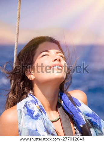 Portrait of happy girl enjoying bright sun light with closed eyes on sailboat in the sea, spending summer vacation on the beach, pleasure and happiness concept - stock photo