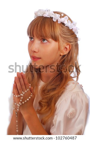 portrait of happy girl going to the first holy communion and posing in studio against white background - stock photo