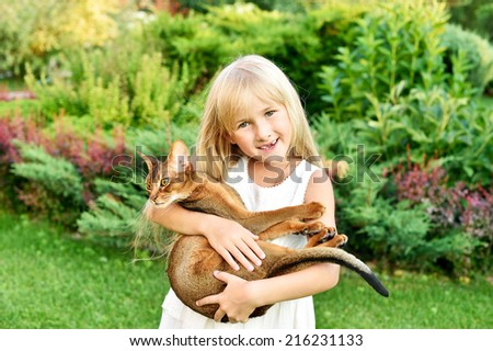 portrait of happy girl holding her abyssinian kitten  happy smiling girl holding her Abyssinian kitten in summer day  - stock photo