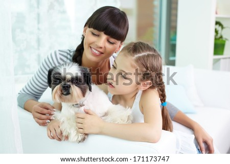 Portrait of happy girl holding pet and looking at it with her mother near by - stock photo