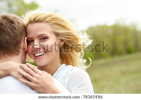Portrait of happy girl hugging her boyfriend outside - stock photo