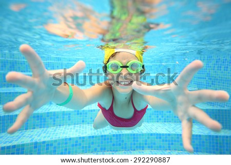 Portrait of happy girl in swimming glasses under water in the pool - stock photo
