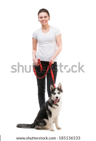 portrait of happy girl in white t-shirt and black trousers isolated on white background and husky dog - stock photo