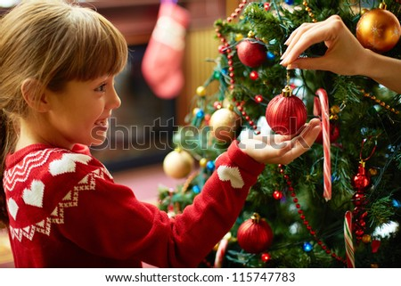 Portrait of happy girl looking at decorative toy ball by Christmas tree - stock photo