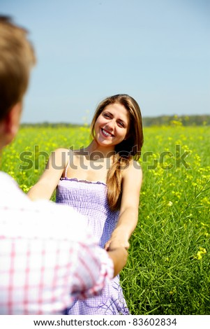 Portrait of happy girl looking at her boyfriend in flower field - stock photo