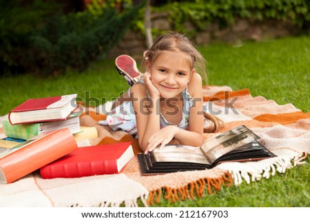 Portrait of happy girl lying on plaid at park and looking at family album - stock photo