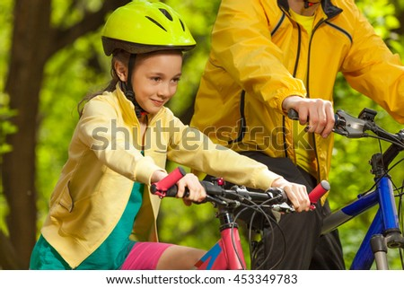 Portrait of happy girl riding her bicycle - stock photo
