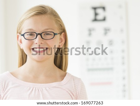 Portrait of happy girl wearing glasses against eye chart in clinic - stock photo