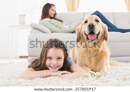 Portrait of happy girl with dog lying on rug while mother relaxing at home - stock photo