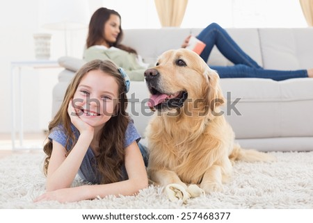 Portrait of happy girl with dog on rug while mother relaxing at home - stock photo