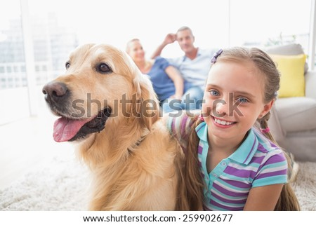Portrait of happy girl with dog while parents relaxing in background at home - stock photo