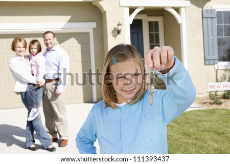 Portrait of happy girl with family holding key in front of new house - stock photo