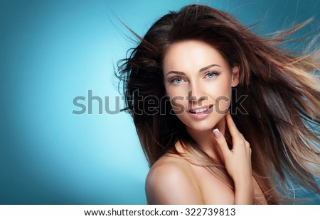 Portrait of happy girl with long dark blowing hair against blue  - stock photo