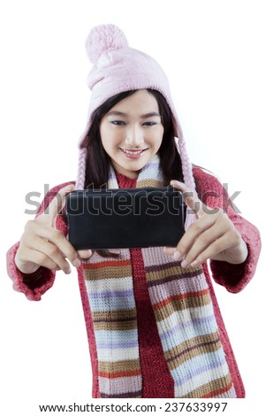 Portrait of happy girl with winter clothes using a mobile phone to take self picture, isolated on white - stock photo