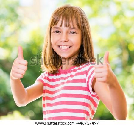 Portrait of happy girl 10-11 year old showing thumbs up gesture. Beautiful schoolgirl posing outdoors. - stock photo