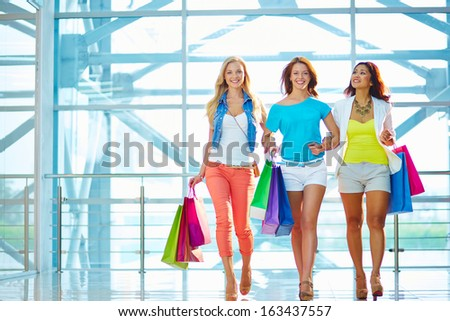 Portrait of happy girlfriends with paperbags walking down trade center - stock photo