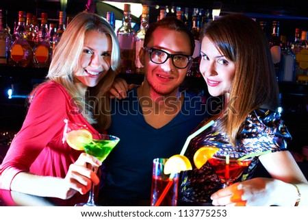 Portrait of happy girls and barman looking at camera at party - stock photo