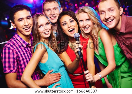 Portrait of happy girls and guys singing in microphone in the karaoke bar  - stock photo