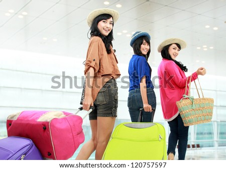 portrait of Happy girls going on vacation walking with suitcase and smile - stock photo