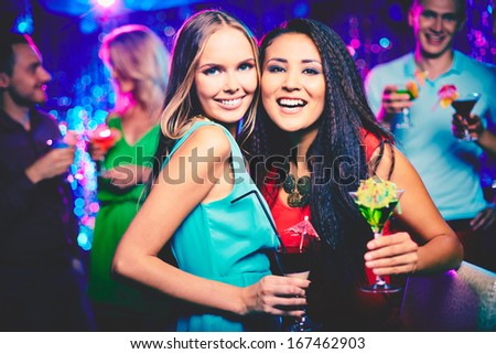 Portrait of happy girls with cocktails looking at camera at party - stock photo