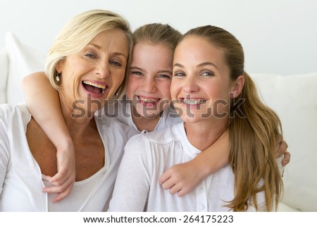 Portrait of happy grandmother, mother and daughter in a white atmosphere. - stock photo