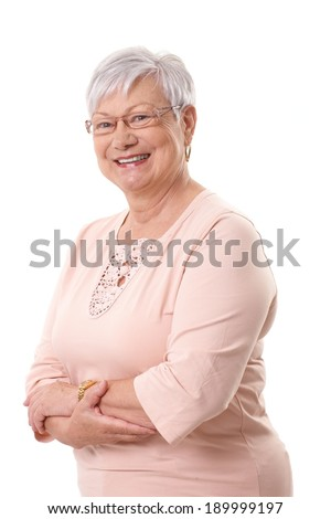 Portrait of happy grandmother smiling at camera, standing arms crossed. - stock photo