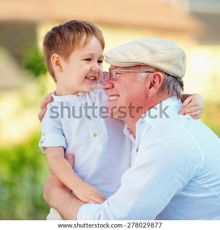 portrait of happy grandpa and his grandson embracing outdoors - stock photo