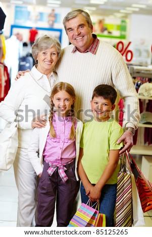 Portrait of happy grandparents and grandchildren during shopping - stock photo