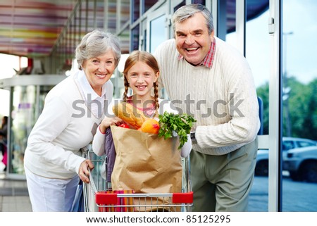 Portrait of happy grandparents and granddaughter near supermarket - stock photo