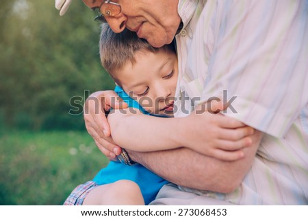 Portrait of happy grandson hugging grandfather over a nature outdoor background. Two different generations concept. - stock photo